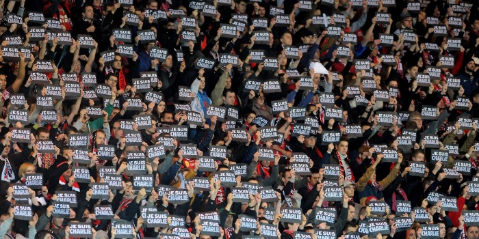 "Guingamp's supporter hold signs reading ""Je suis Charlie"" (I am Charlie) to pay tribute to the victims of the Charlie Hebdo attack during the French L1 football match between Guingamp and Lens at the Roudourou stadium in Guingamp, western France, on January 10, 2015.  AFP PHOTO / FRED TANNEAU        (Photo credit should read FRED TANNEAU/AFP/Getty Images)"